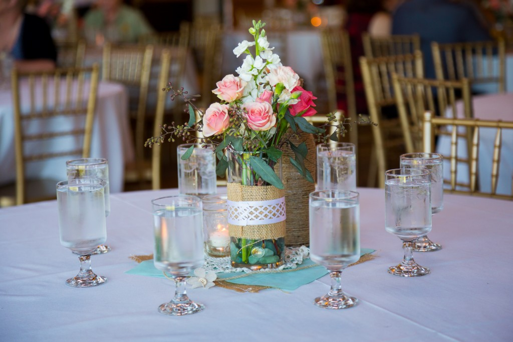 DIY wedding decor table centerpieces with wine bottles wrapped in burlap twine and rose flowers.